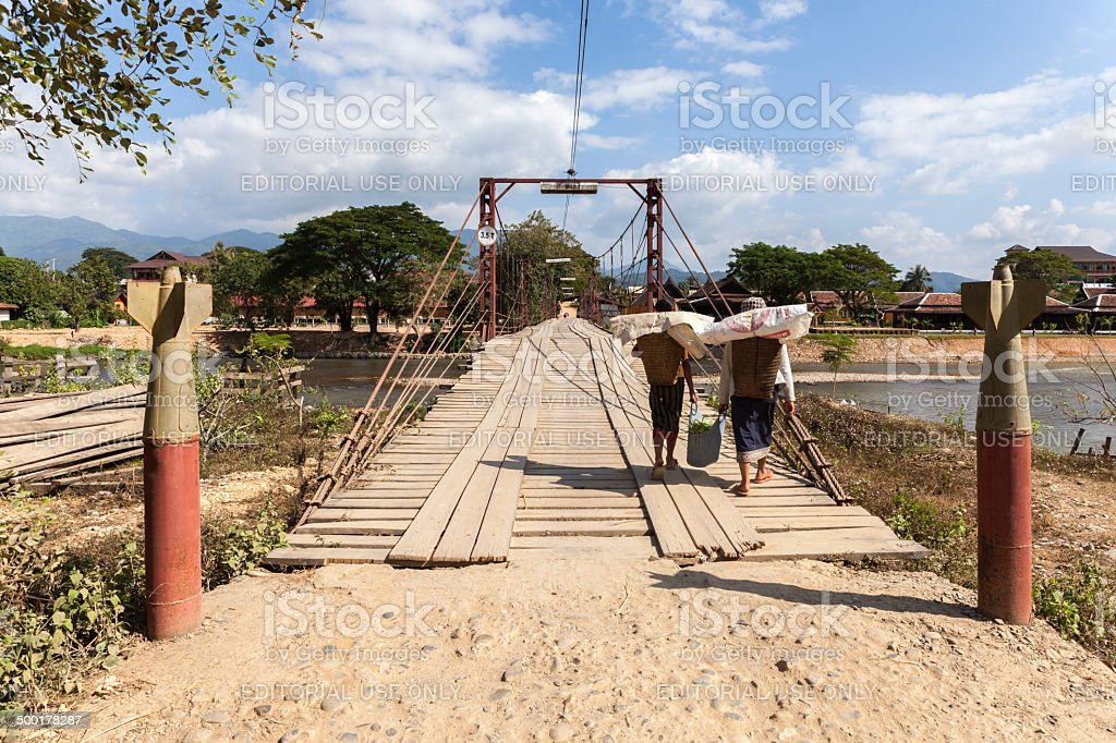 Two Laotian women crossing a bridge in Vang Vieng stock photo