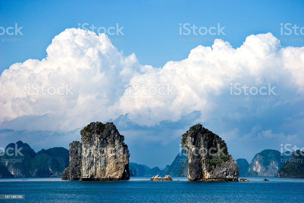 Two large rock structures in Halong Bay under fluffy clouds royalty-free stock photo