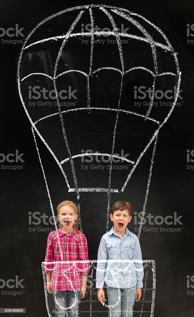 two laughing schoolchildren flying on imaginary drawn air baloon stock photo