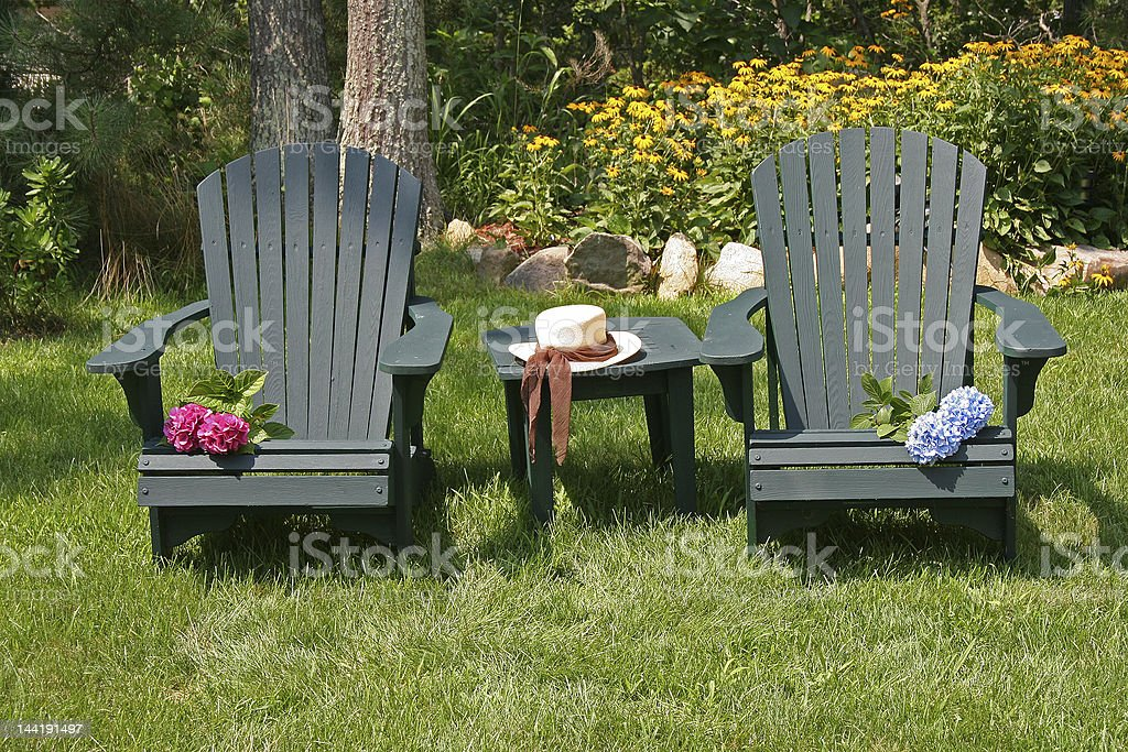 two lawn chairs in a garden royalty-free stock photo