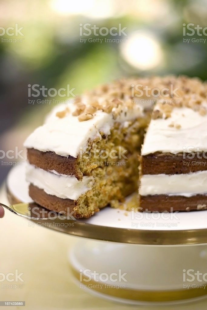 Two layer carrot cake being sliced and served royalty-free stock photo