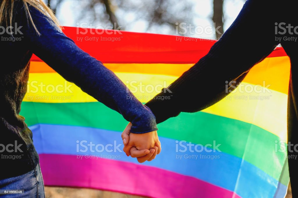 Two lesbian girls holding hands and rainbow flag stock photo