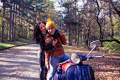 Two lesbian girls siting and huging on motorcycle in nature
