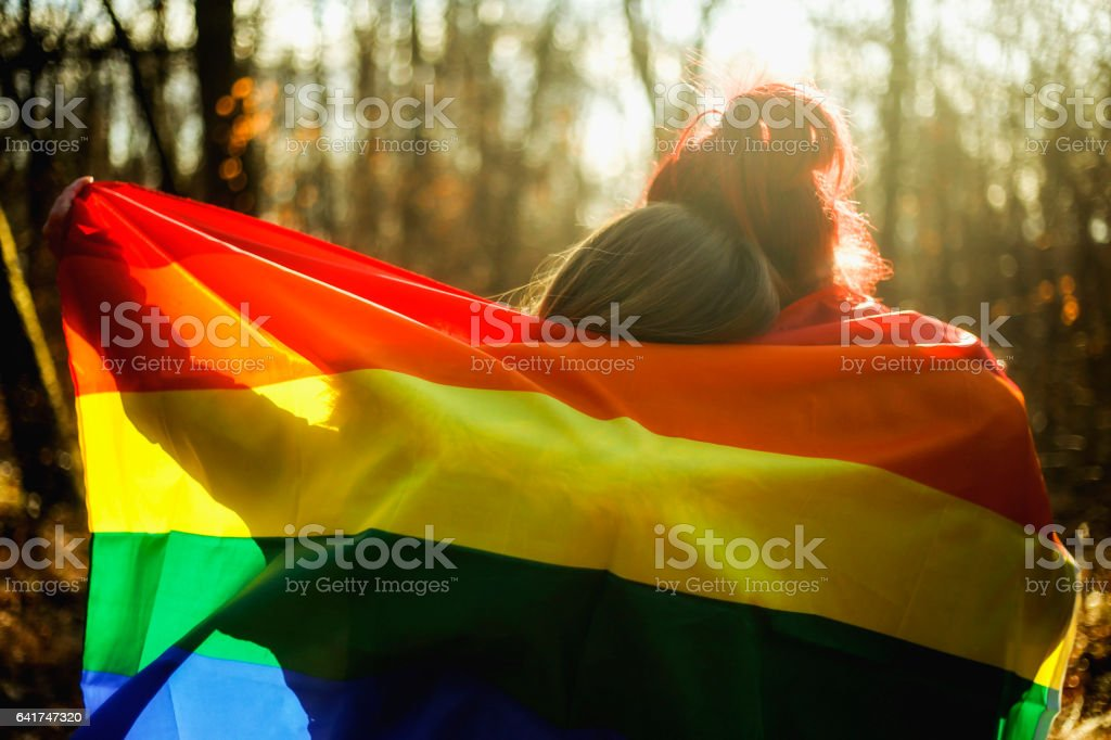 Two lesbians are embracing the gay flag stock photo