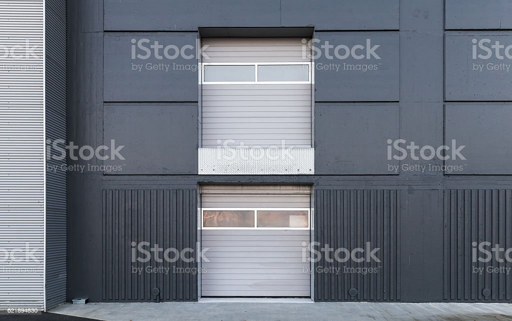 Two level closed gates in gray metal wall stock photo