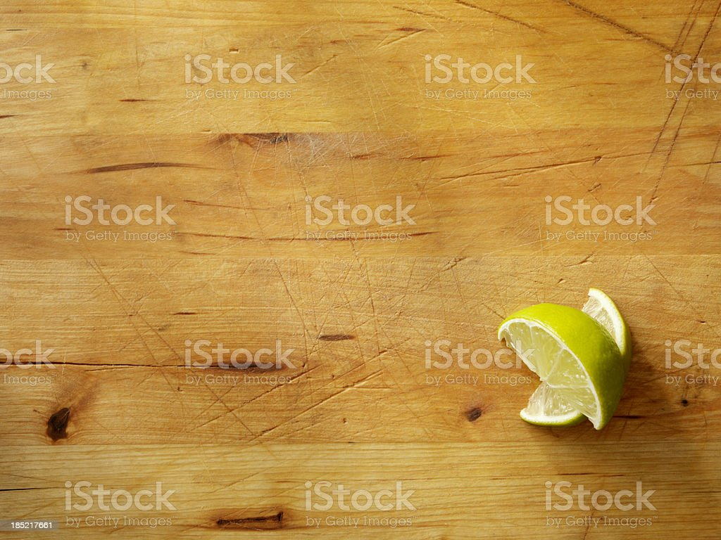 Two lime wedges on a wooden cutting board royalty-free stock photo