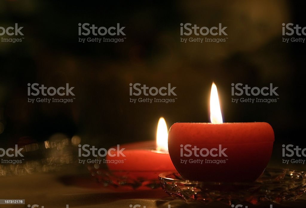 Two lit red candles on a table royalty-free stock photo