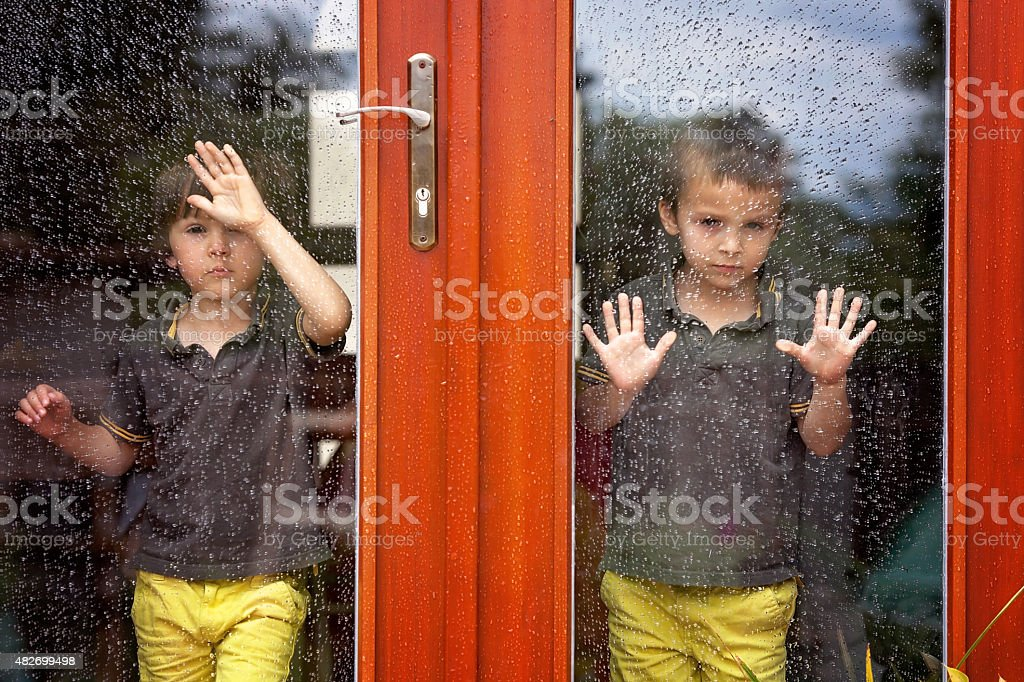 Two little boy, wearing same clothes looking through big glass stock photo