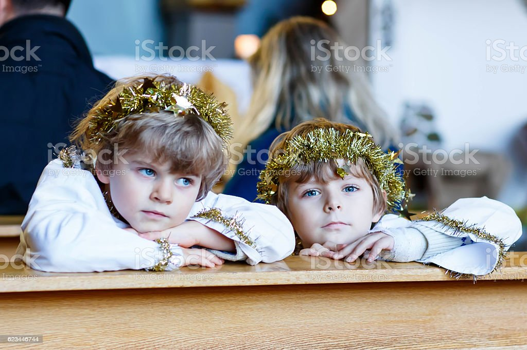 Two little boys angels of Christmas story eve in church stock photo
