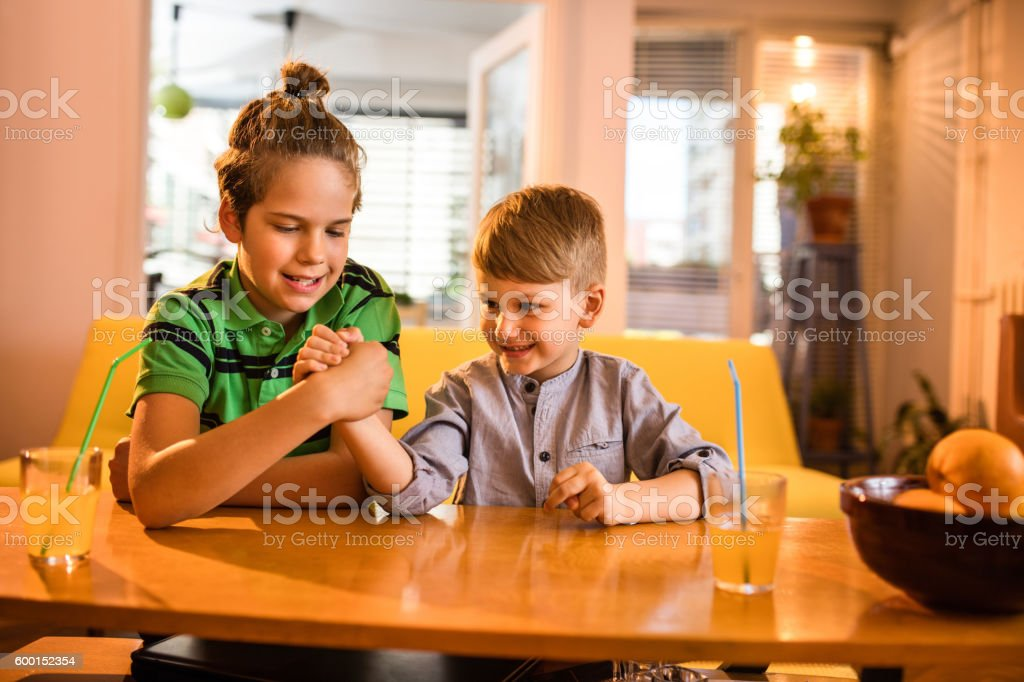 Two little boys arms wrestling in the living room. stock photo