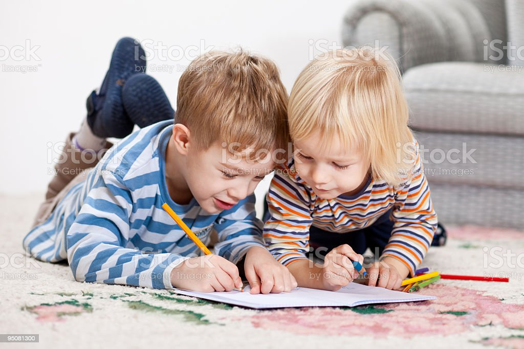 Two little boys drawing in the notepad royalty-free stock photo