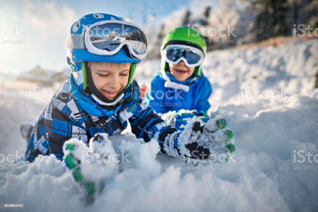 Two little boys in ski outfits playing in snow stock photo