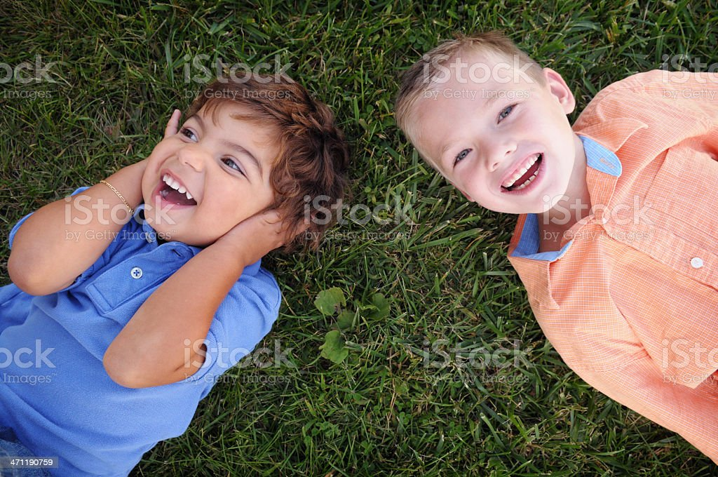 Two Little Boys Lying in the Grass Laughing royalty-free stock photo