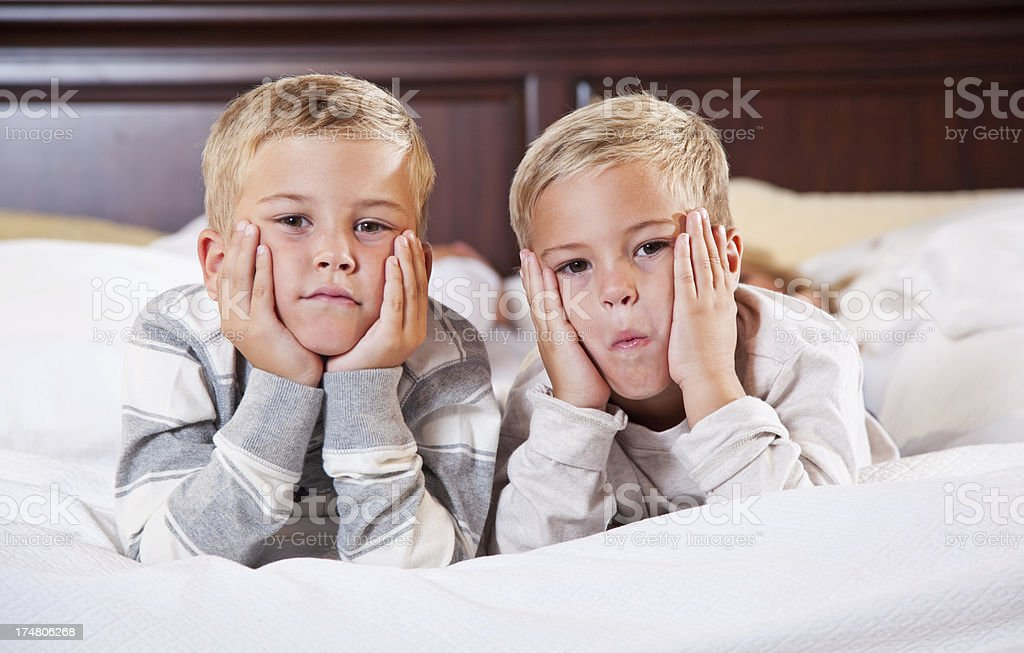 Two little boys lying on bed stock photo