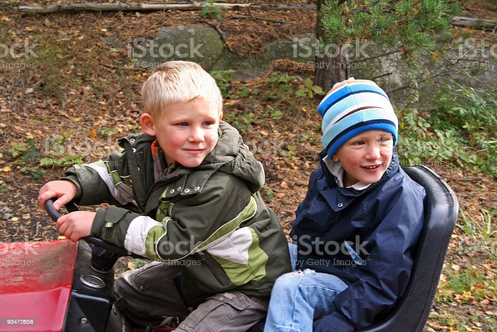 Two little boys on a tractor watching something interesting royalty-free stock photo