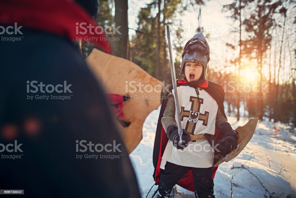 Two little boys playing knights stock photo