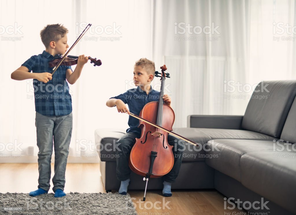 Two little boys practicing cello and violin together stock photo