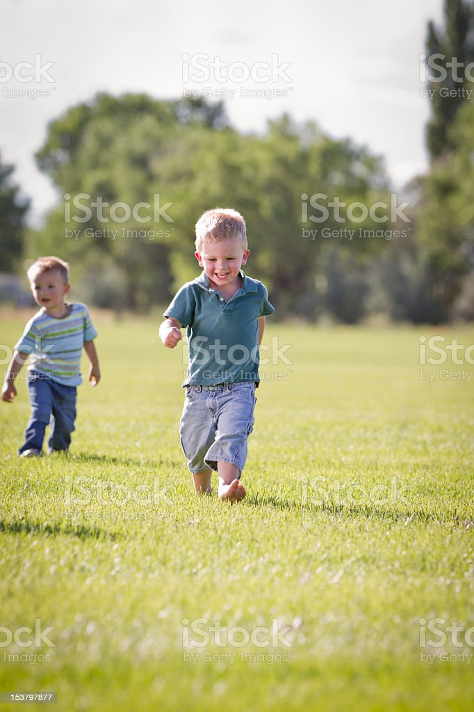 Two Little Boys Running in a Field stock photo