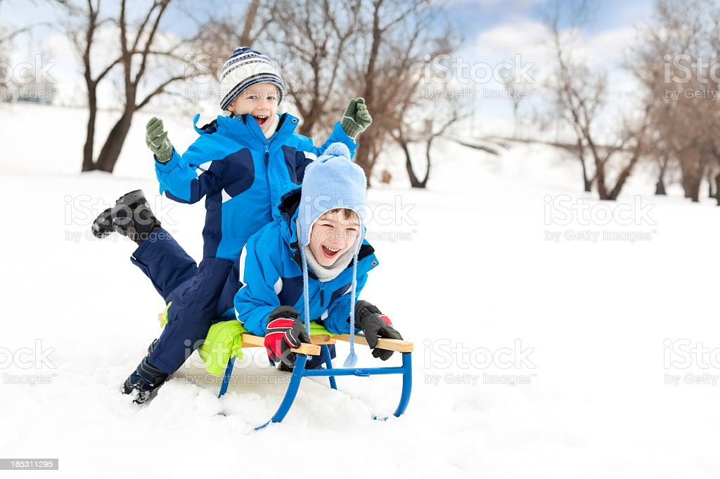 Two little boys sledding on snow in the park royalty-free stock photo