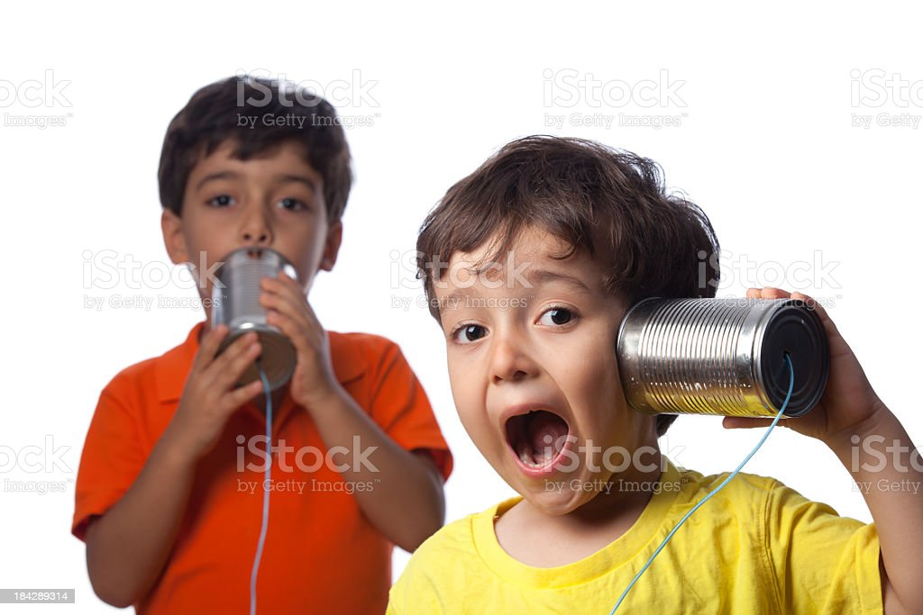 Two Little Boys Talking And Communicating On Tin Can Phone stock photo