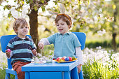 Two little boys wearing Easter bunny ears, painting colorful egg
