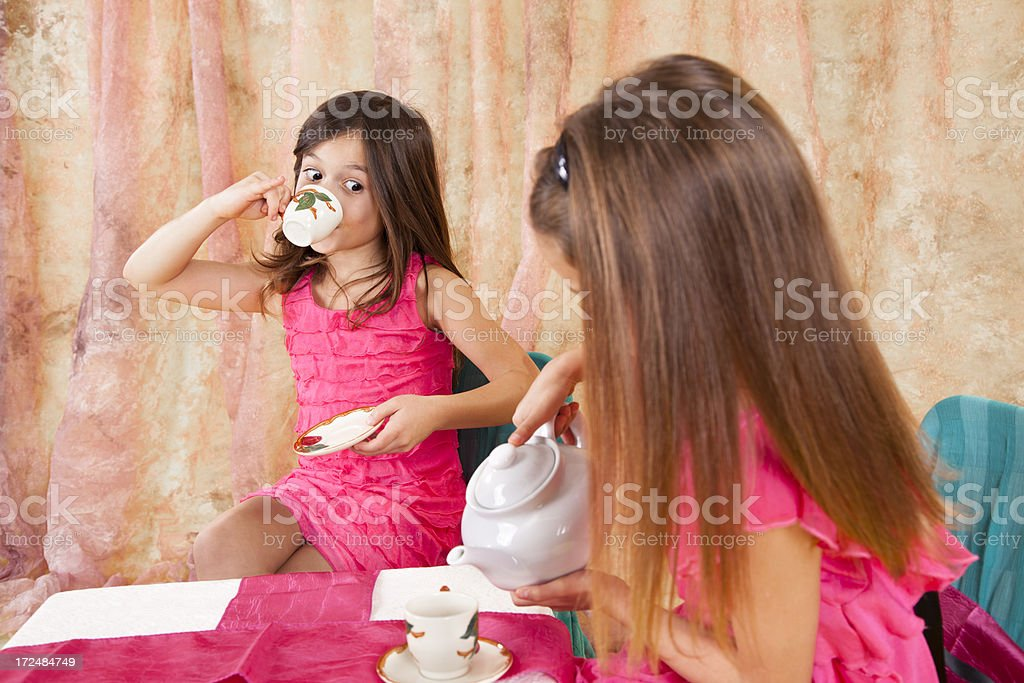 Two little Caucasian girls 7-8, playing tea party teapot teacups royalty-free stock photo