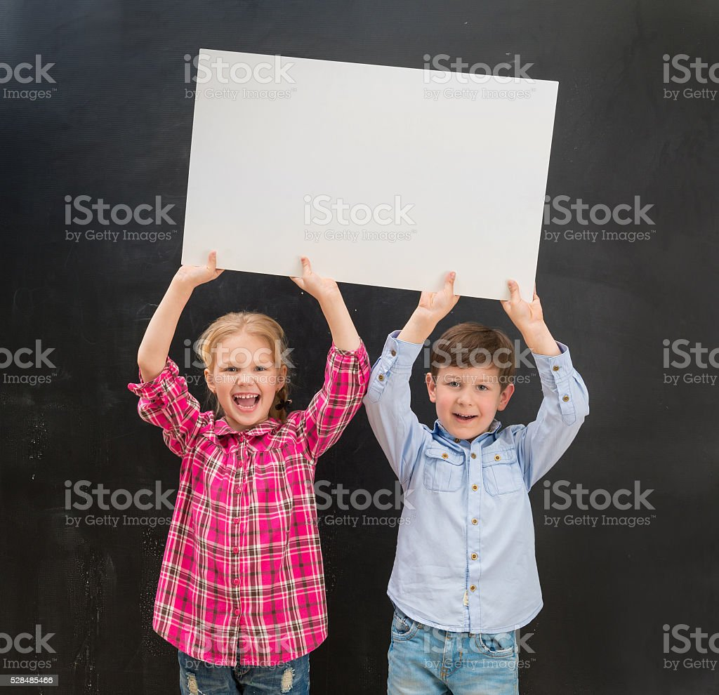 two little children keeping blank paper sheet above their heads stock photo