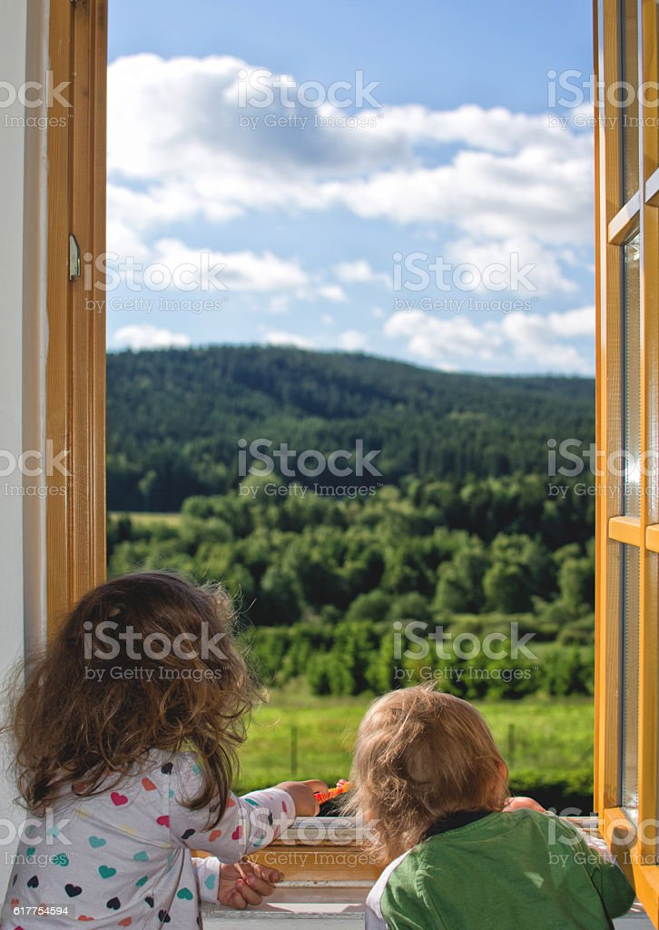 Two little children looking out the window stock photo