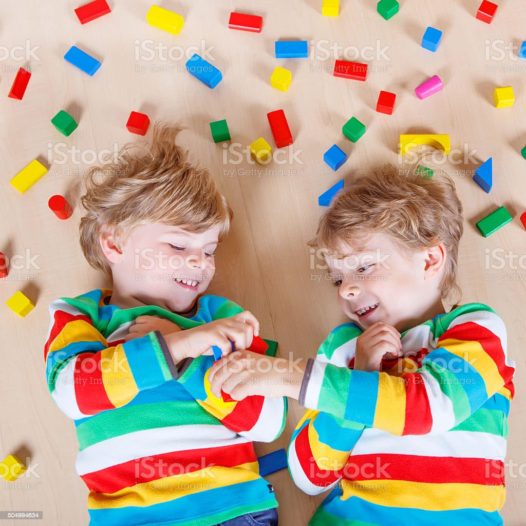 Two little children playing with colorful wooden blocks indoor stock photo
