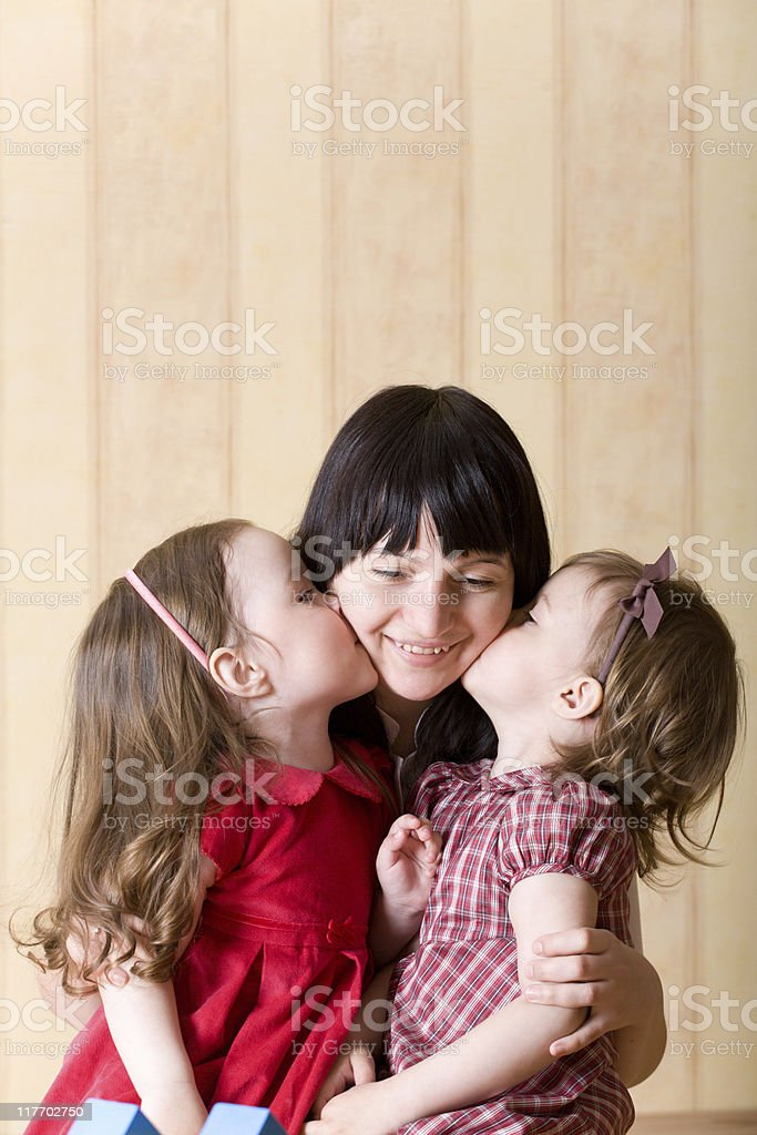 Two little daughter kiss their mother stock photo