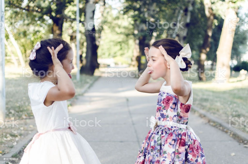 two little friends  tongues out at each other stock photo