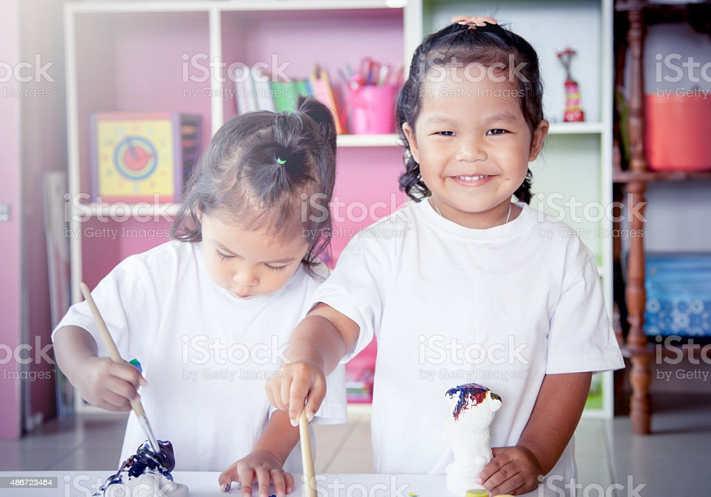 Two little girl having fun to paint on stucco doll stock photo