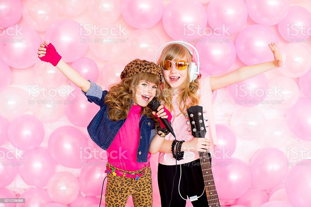 two little girl with a microphone stock photo