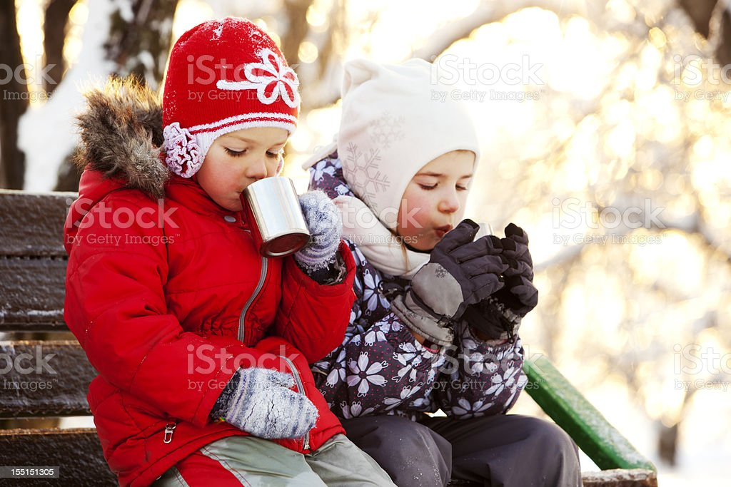Two Little Girls Drinking Hot Tea in Winter Park royalty-free stock photo