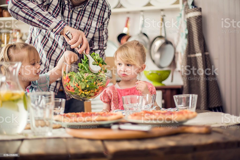 Two Little Girls Eating Pizza with Fresh Salad stock photo