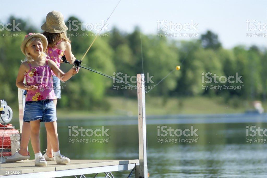 Two little Girls Fishing on Lake Dock royalty-free stock photo