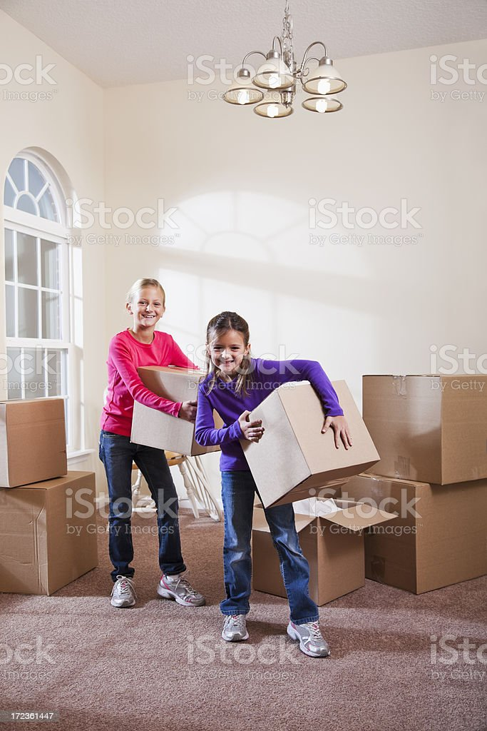 Two little girls helping move boxes stock photo