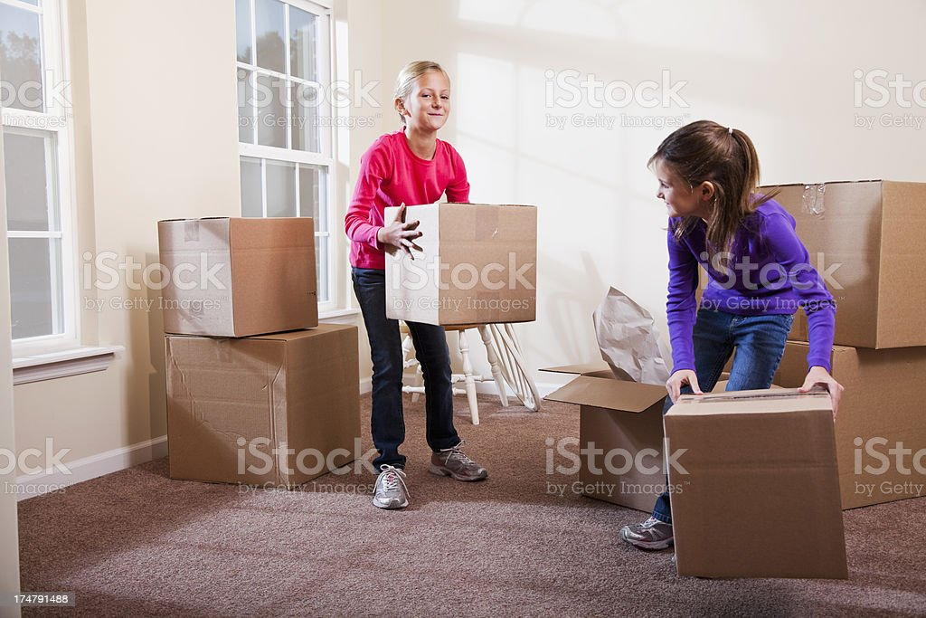 Two little girls helping move boxes royalty-free stock photo