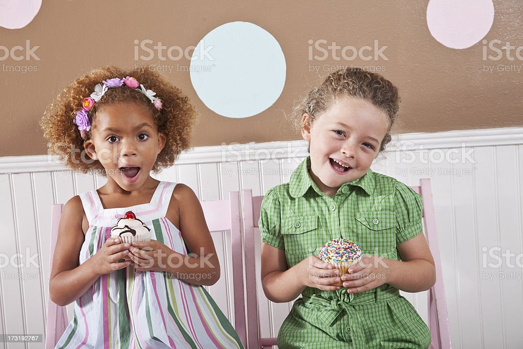 Two little girls holding cupcakes stock photo