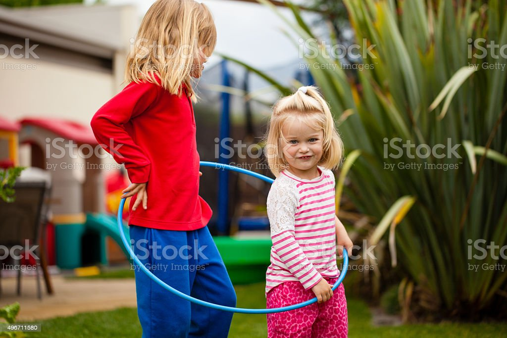 Two little girls in a hula hoop stock photo