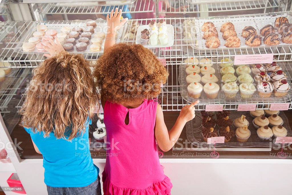 Two little girls in bakery stock photo