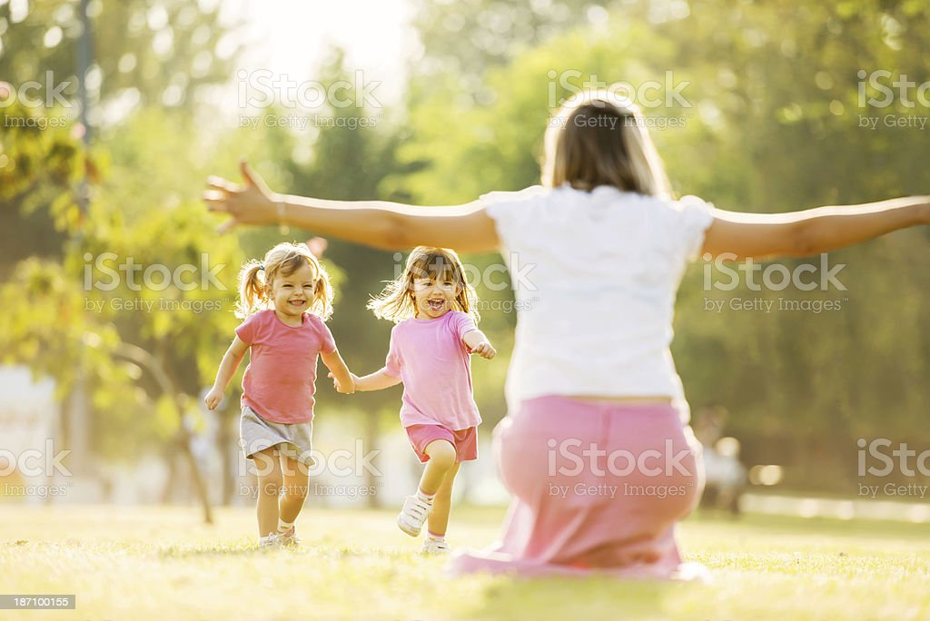 Two little girls in pink running toward their mom stock photo