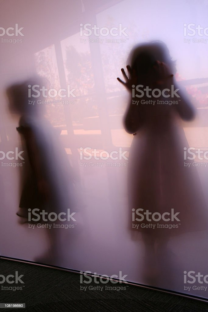 Two little girls in Silhouette behind frosted glass stock photo