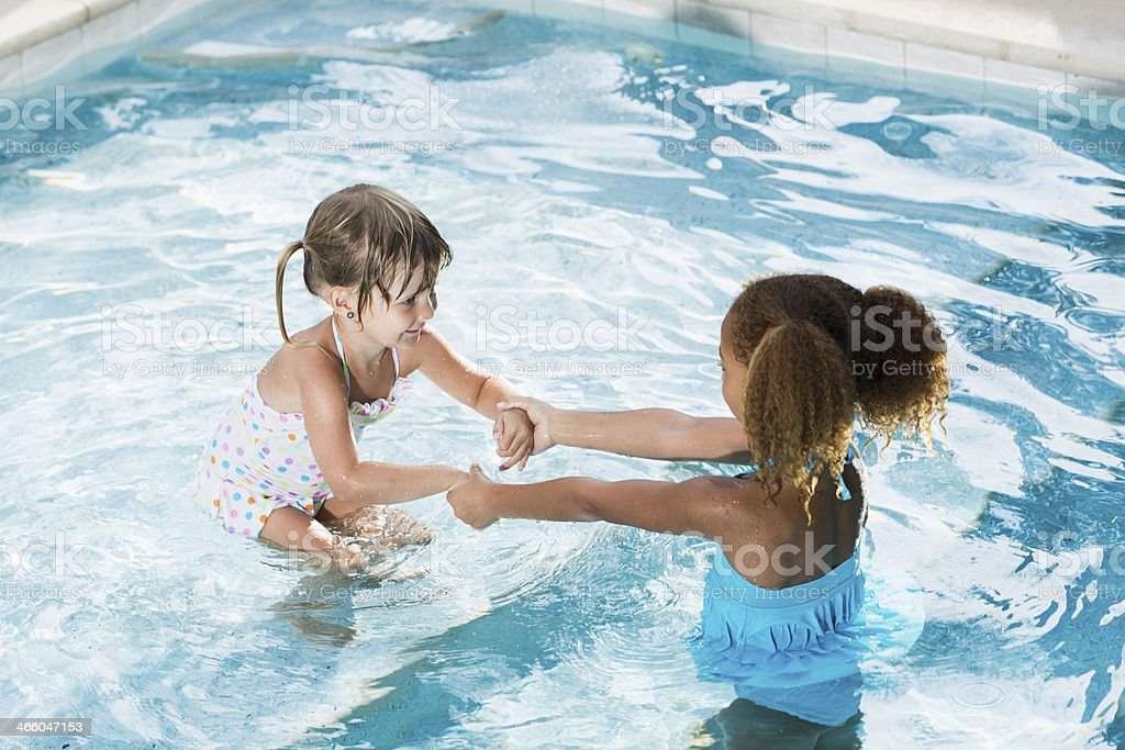 Two little girls in swimming pool royalty-free stock photo