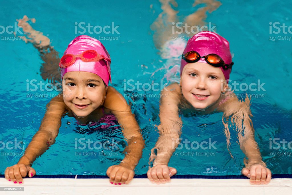 Two little girls in swimming pool stock photo