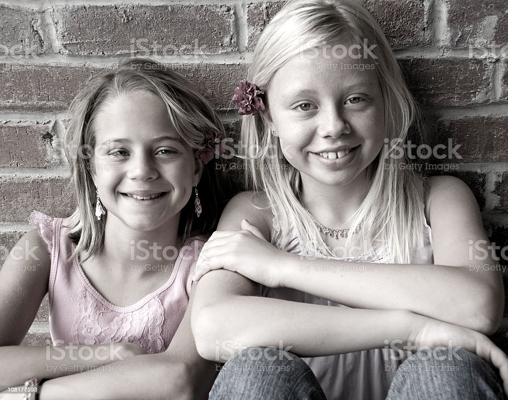 Two Little Girls Leaning on Brick Wall royalty-free stock photo