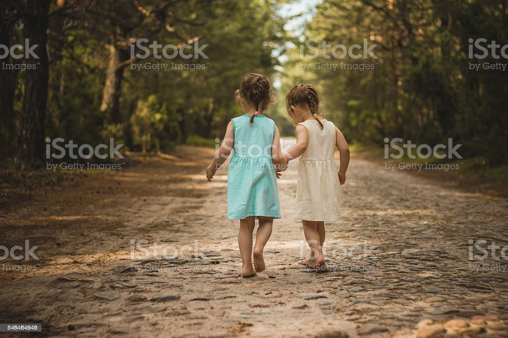 Two little girls on a forest road stock photo