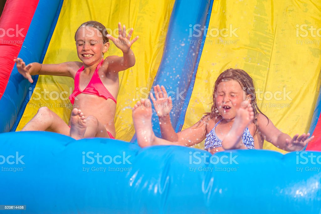 Two little girls on an inflatable slide stock photo