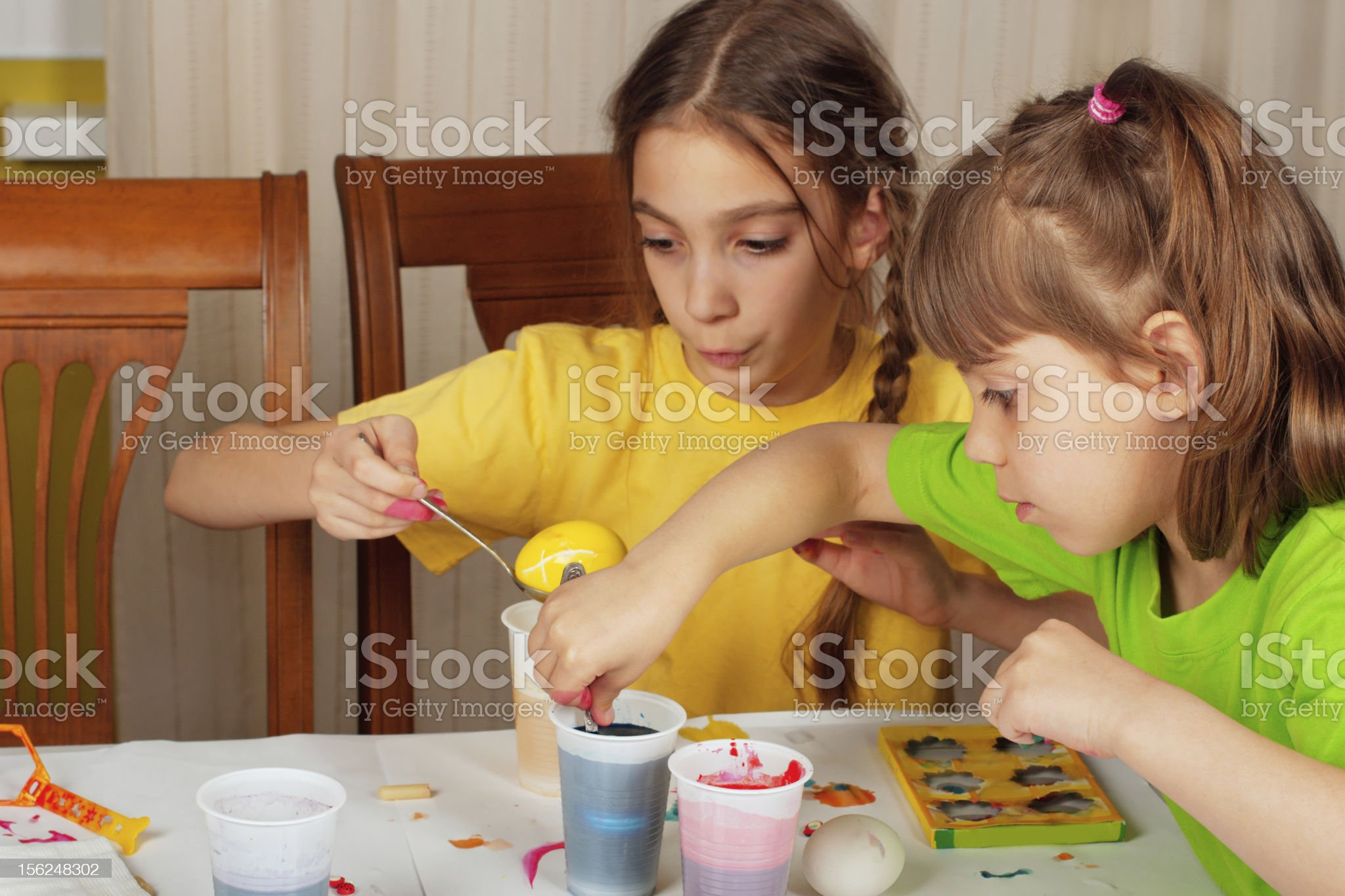 Two little girls (sisters) painting on Easter eggs royalty-free stock photo