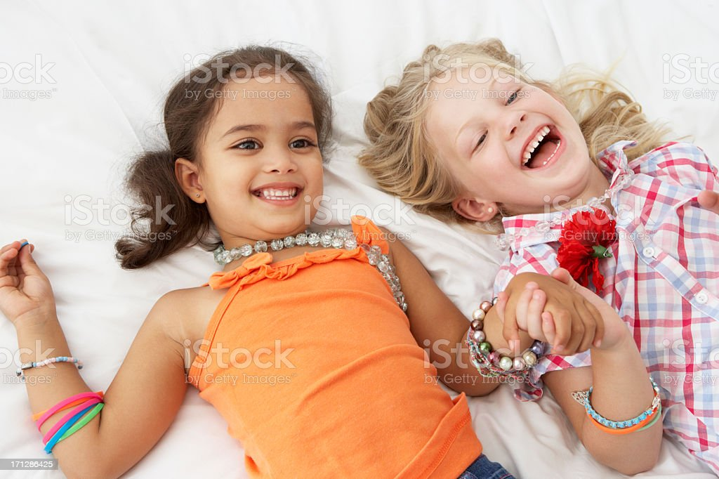 Two little girls playing dress up with jewelry and laughing stock photo